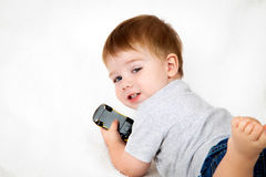 Boy Playing With Toy Car. Little boy laying on his stomach, playing with a toy car.  He seems to have been inerrupted Stock Image