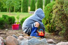 Boy playing with toy car outdoors stock photo