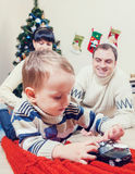 Boy playing with toy cars with his parents under the christmas t Stock Photo