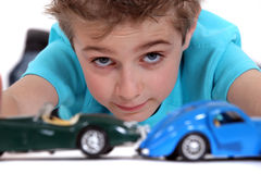 Boy playing with toy cars Stock Photos
