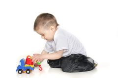 Boy playing with toy crane over white Royalty Free Stock Photos