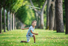 Boy playing with toy glider in park Royalty Free Stock Photos