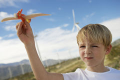 Boy Playing With Toy Glider At Wind Farm Stock Photo