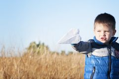 A boy is playing with a toy paper airplane against the blue sky in the field Stock Images