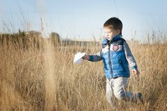 A boy is playing with a toy paper airplane against the blue sky in the field Royalty Free Stock Image