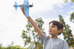 Boy playing with a toy plane at park Royalty Free Stock Image