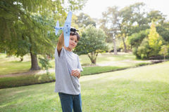 Boy playing with a toy plane at park Stock Photos