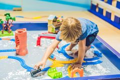 A boy is playing with a toy railroad royalty free stock images
