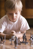 Boy Playing With Toy Soldiers On Floor Royalty Free Stock Photography