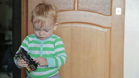 Boy playing with toy train. Little boy playing with toy train sitting on the floor stock footage