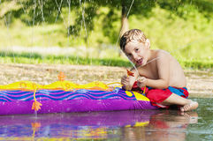 Boy playing with toy water sprinkler. Boy having fun  pointing water with toy sprinkler and smiling Stock Images