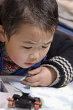 Boy playing with toys. Picture of a little chinese boy playing with toys with great attention Royalty Free Stock Photos