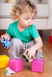 Boy playing with toys on the floor Stock Photo