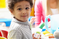 Boy playing with toys in nursery. Smiling at camera royalty free stock photo