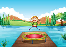 A boy playing with the trampoline at the river Royalty Free Stock Photography