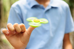 Boy playing with a Tri Fidget Hand Spinner Stock Images