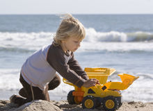 Boy playing with trucks. A young boy playing with trucks on the beach stock images