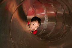 Boy playing in a tube slide Royalty Free Stock Photo