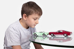 Boy playing with two toy cars Royalty Free Stock Photos