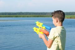 Boy playing with two water pistols on the street in summer stock image