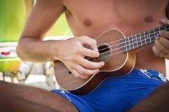 Boy playing the ukulele stock photo