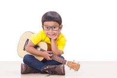 Boy playing ukulele Royalty Free Stock Photos