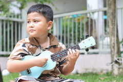 Boy playing the ukulele Stock Photos