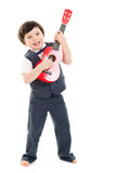 Boy playing ukulele. Handsome boy in a grey suit and on bare feet playing a red ukulele against a white background Stock Photo