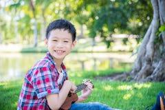 Boy playing ukulele in park Royalty Free Stock Photography