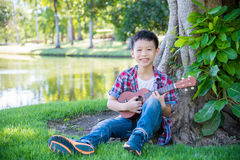Boy playing ukulele in park Stock Photos