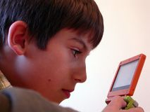 Boy playing video game 3. A young boy playing a handheld video game Royalty Free Stock Images