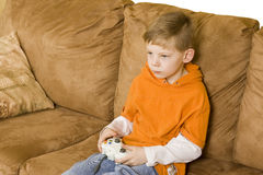 Boy playing video game. Here is a young boy sitting on a couch playing a video game Stock Photos