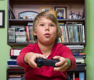 Boy   playing a video game console. Boy teenager with remote control in hand playing a video game console Stock Photography