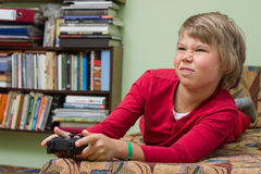 Boy   playing a video game console. Boy teenager with remote control in hand playing a video game console Stock Photos