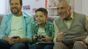 Boy playing video game, father and grandpa holding gadgets supporting child