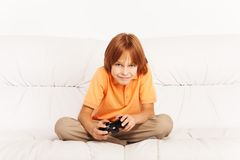 Boy playing video game. Happy Caucasian boy playing video games holding game controller sitting on the coach in living room Stock Images