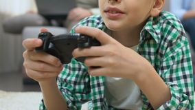 Boy playing video game at home, family using gadgets on background, addiction