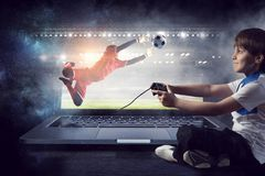 Boy playing a video game. Mixed media Royalty Free Stock Photography
