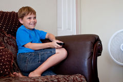 Boy playing video game on TV. An 8 year-old boy with dark blonde hair holds a remote control as he is playing a wii video game on TV.  The remote could also Royalty Free Stock Images