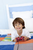 Boy playing video games. Portrait of boy playing video games in bed Royalty Free Stock Image