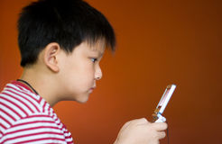 Boy playing video games. On a portable video game device Stock Photo