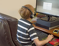 Boy Playing Video Games on Computer. Boy wearing headset while playing video games on office computer Stock Images
