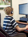 Boy Playing Video Games on Computer. Boy wearing headset while playing video games on office computer Stock Photography