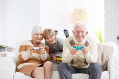 Boy playing video games. With his grandparents Royalty Free Stock Image