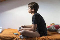 Boy playing video games at home. Young boy playing video games sitting on the bed in her room while charging the phone Royalty Free Stock Image