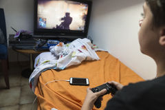 Boy playing video games at home. Young boy playing video games sitting on the bed in her room while charging the phone Stock Image