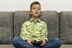 Boy playing video games with joystic sitting on sofa. Boy playing video games with joystic sitting on the grey sofa Stock Image