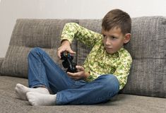 Boy playing video games with joystic sitting on sofa. Boy playing video games with joystic sitting on the sofa Stock Image