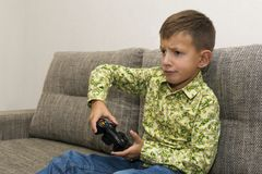 Boy playing video games with joystic sitting on sofa. Boy playing video games with joystic sitting on the sofa Stock Photography