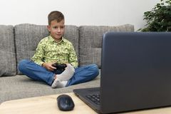 Boy playing video games with joystic sitting on sofa. Boy playing video games with joystic sitting on the sofa Stock Photos